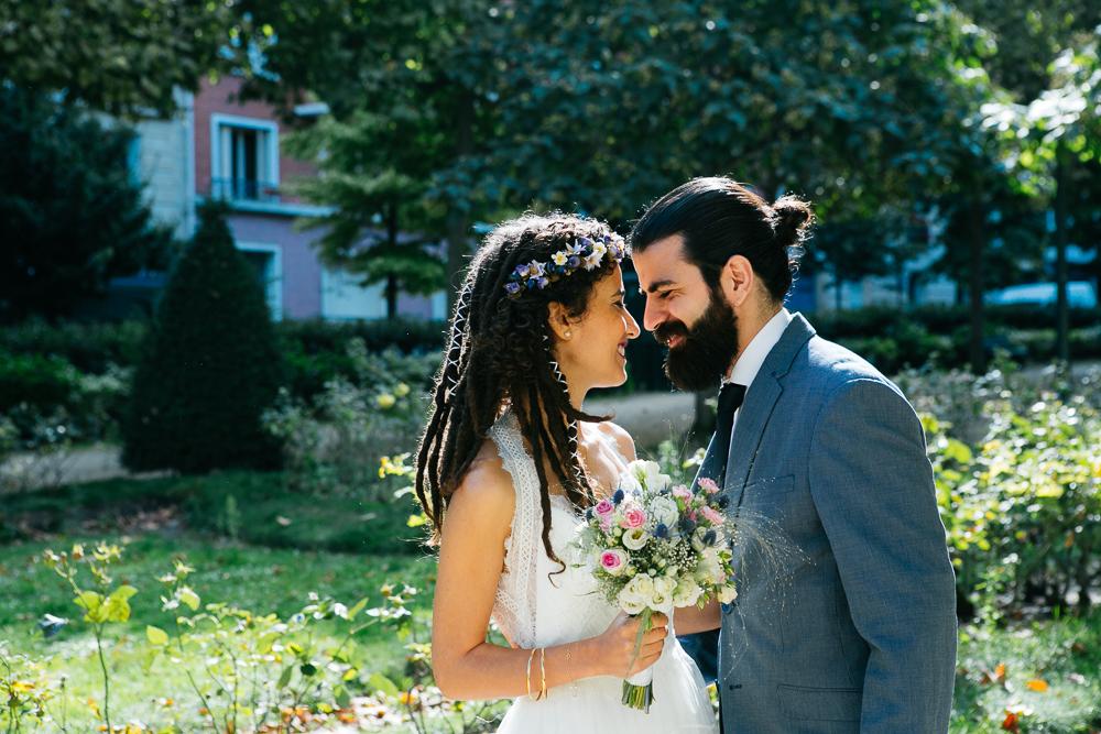 une mariée avec des dreadlocks et un marié hipster s'enlacent au pont de Bir Hakeim Paris
