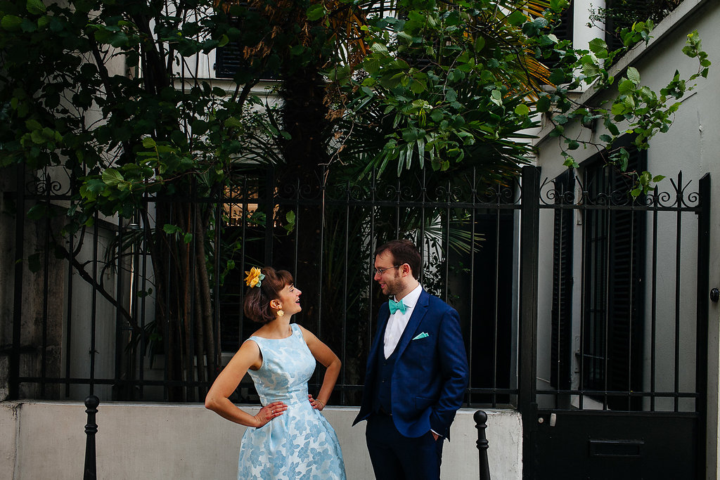 Mariée en robe bleue vintage et son mari en costume bleu se souriant dans une rue de Paris XIVème arrondissement