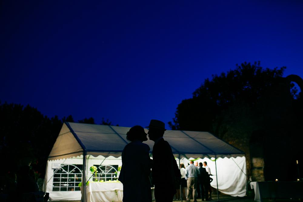 Photo couleur des mariés s'embrassant à l'écart de leurs invités