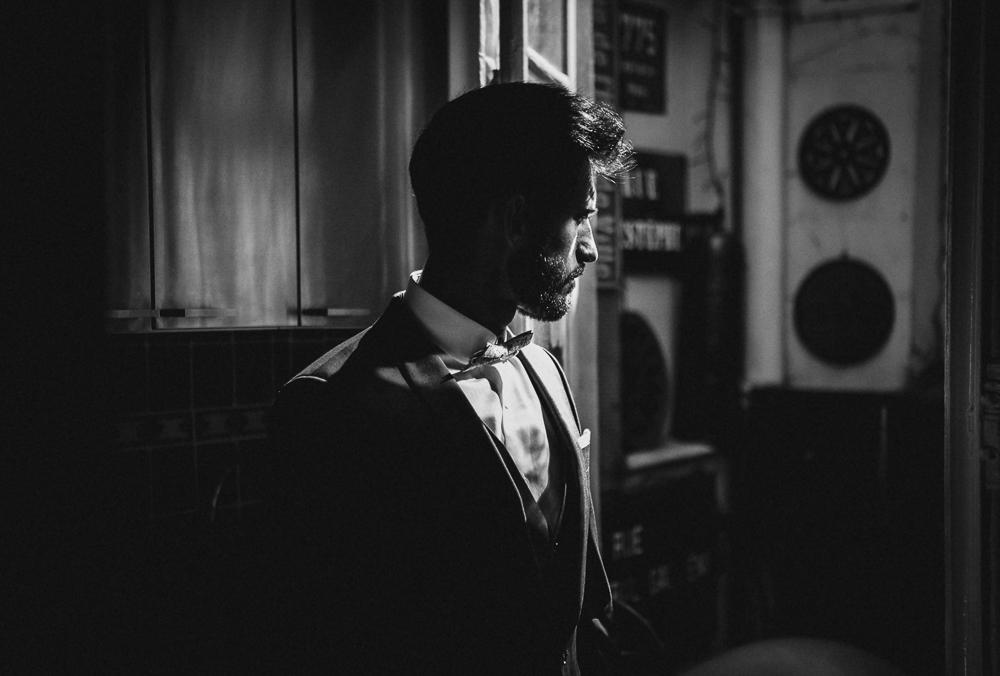 Portrait en noir et blanc du marié à la fin des préparatifs