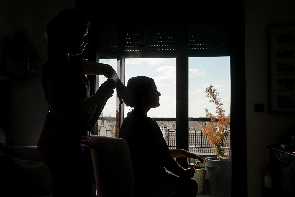 La coiffeuse pose de la laque dans le chignon de la future mariée