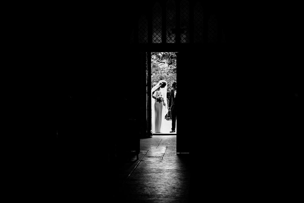 Photo en noir et blanc de la mariée et de son père à l'entrée de l'Eglise