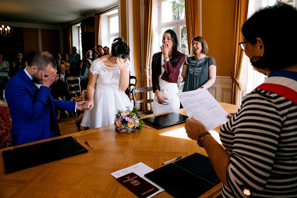 photo prise pendant la cérémonie civile montrant les mariés embarrassés et les témoins riant