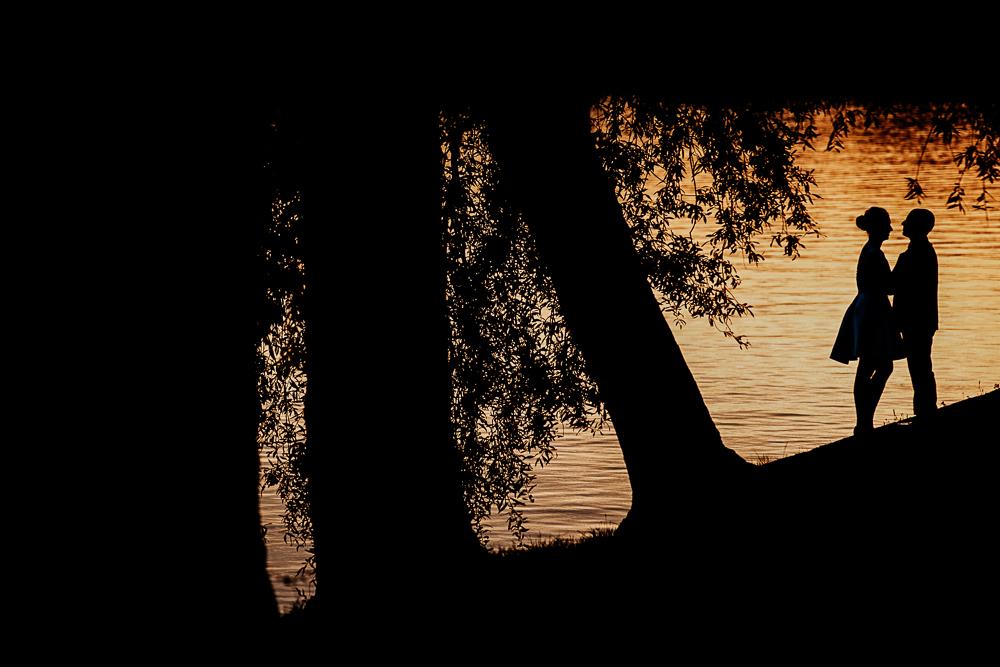 silhouette de mariés au soleil couchant en bord de l'eau
