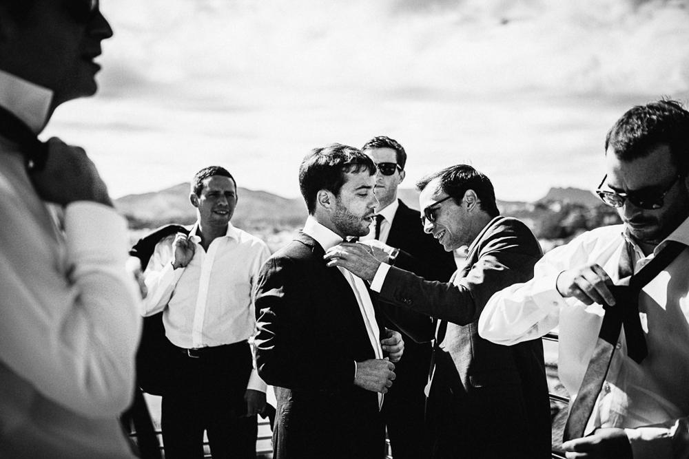 photo en noir et blanc d'un témoin aidant le marié avec son noeud papillon