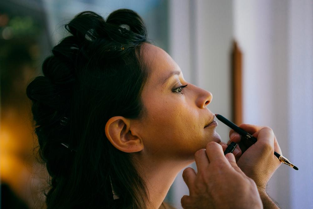 pose du rouge à lèvre par le maquilleur pendant les préparatifs de la mariée