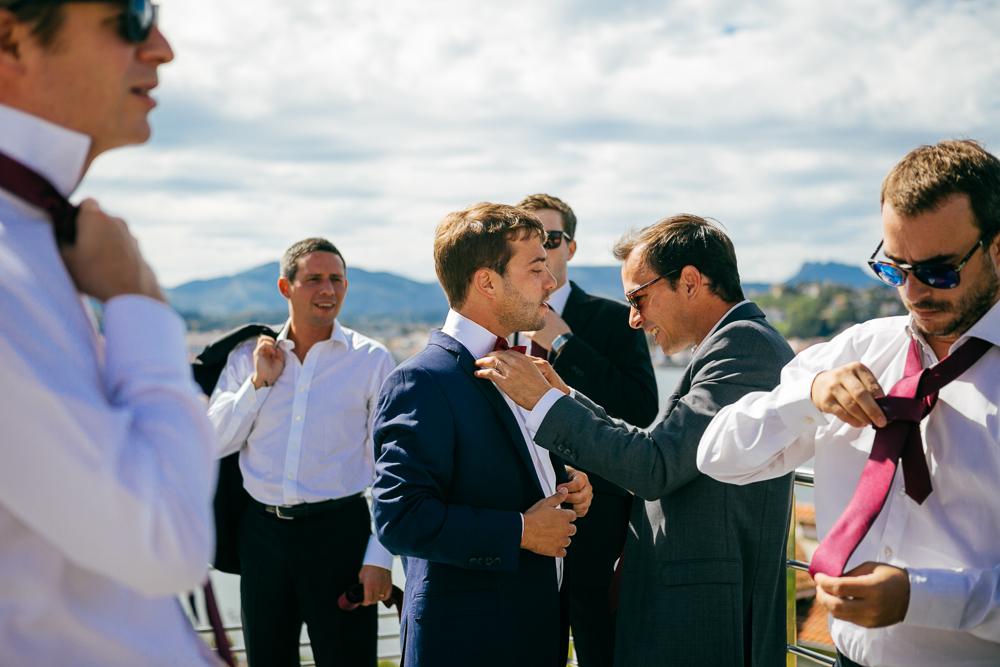 un témoin aide le marié avec son noeud papillon sur la terrasse de la maison à St Jean de Luz