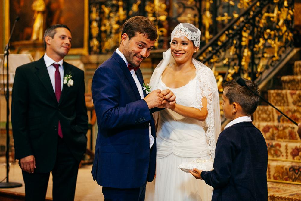 le marié passe l'alliance au doigt de la mariée un air amusé
