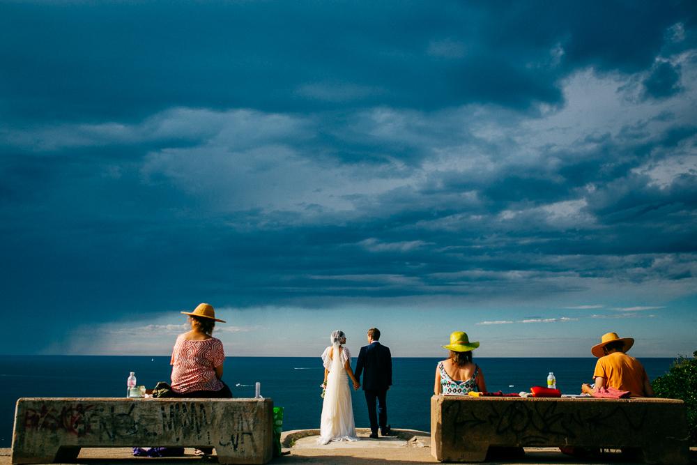 photo de couple marié en bord de l'océan avec un ciel orageux
