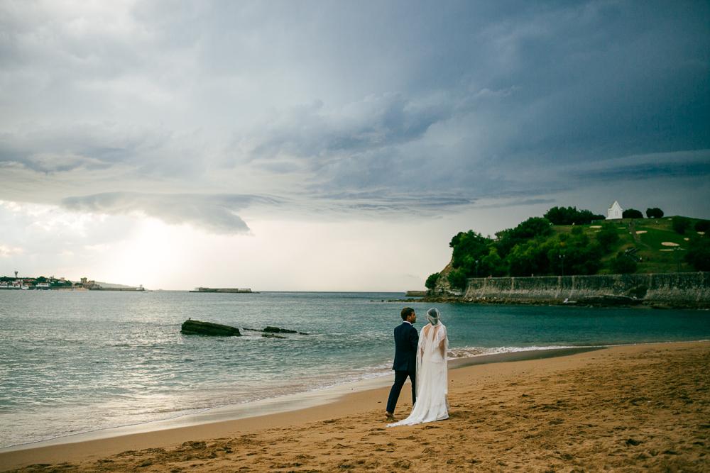 un couple marié marchant sur la plage basque, l'orage arrive