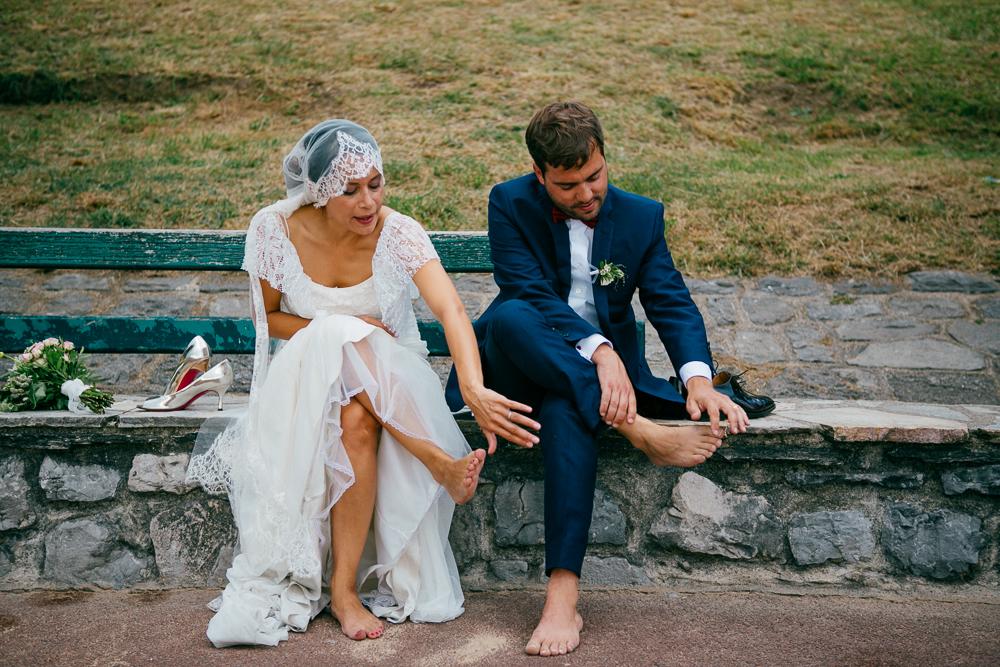 la mariée et le marié se nettoient les pieds après avoir marché sur la plage de St Jean de Luz