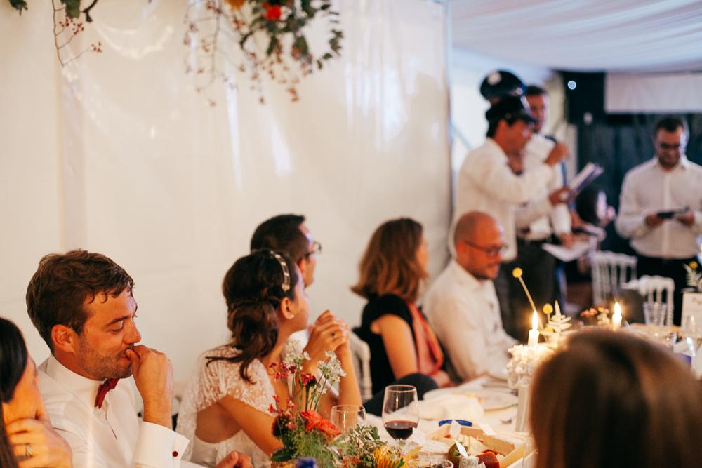 la marié se pince la bouche à l'écoute du discours de ses mariés pendant le diner de mariage sous tente blanche